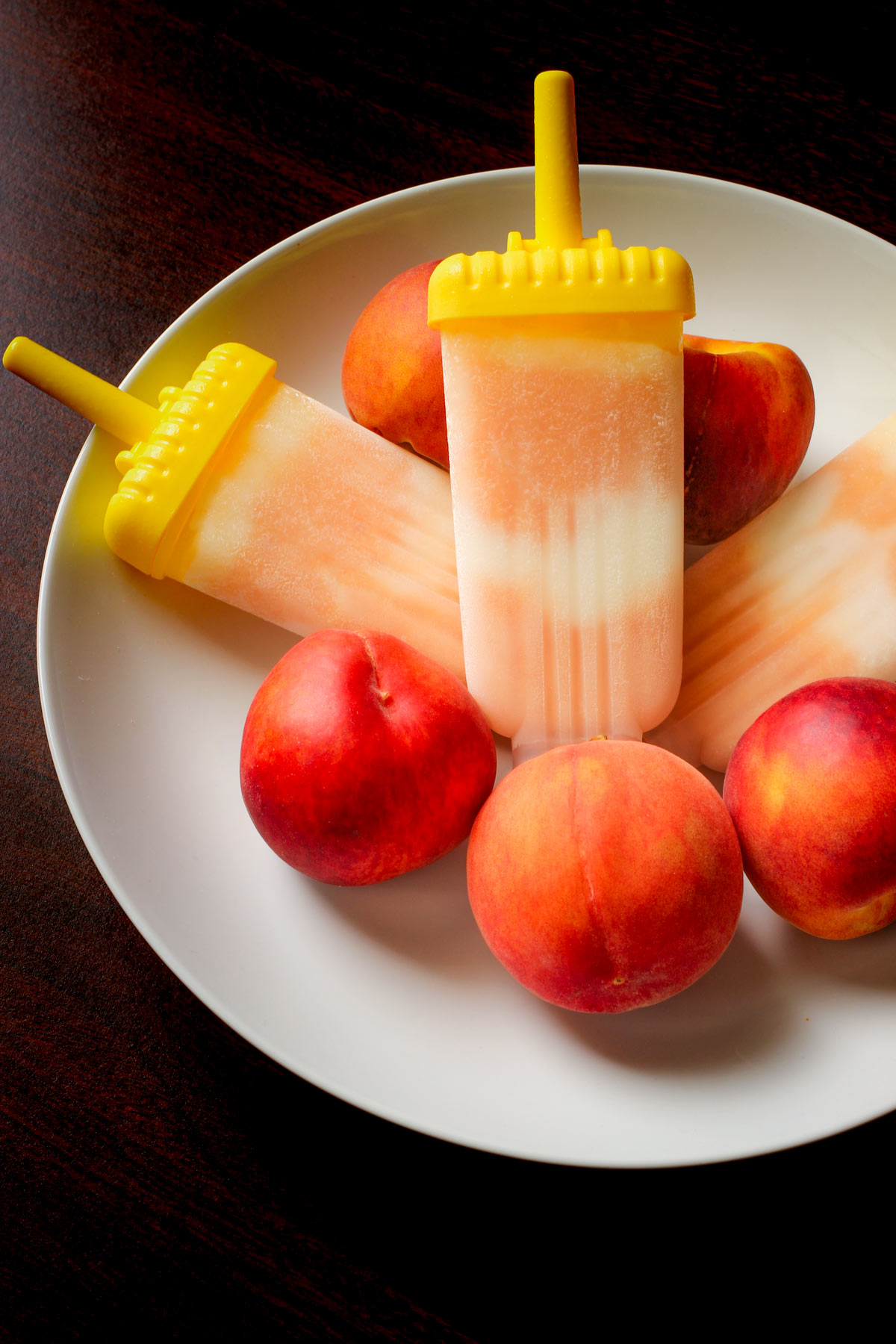 yogurt popsicles in molds in bowl of peaches.
