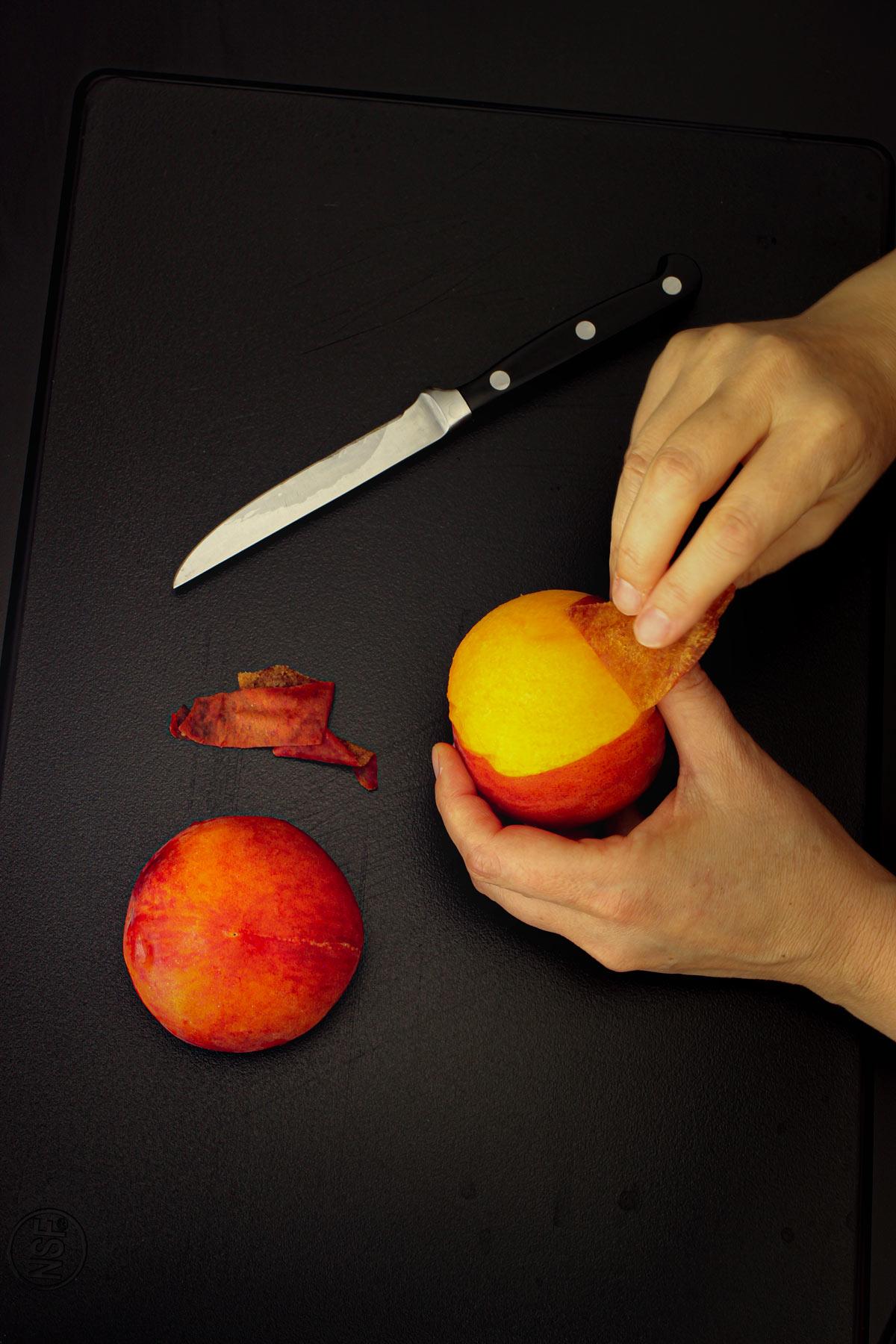 hand peeling skin from peach.