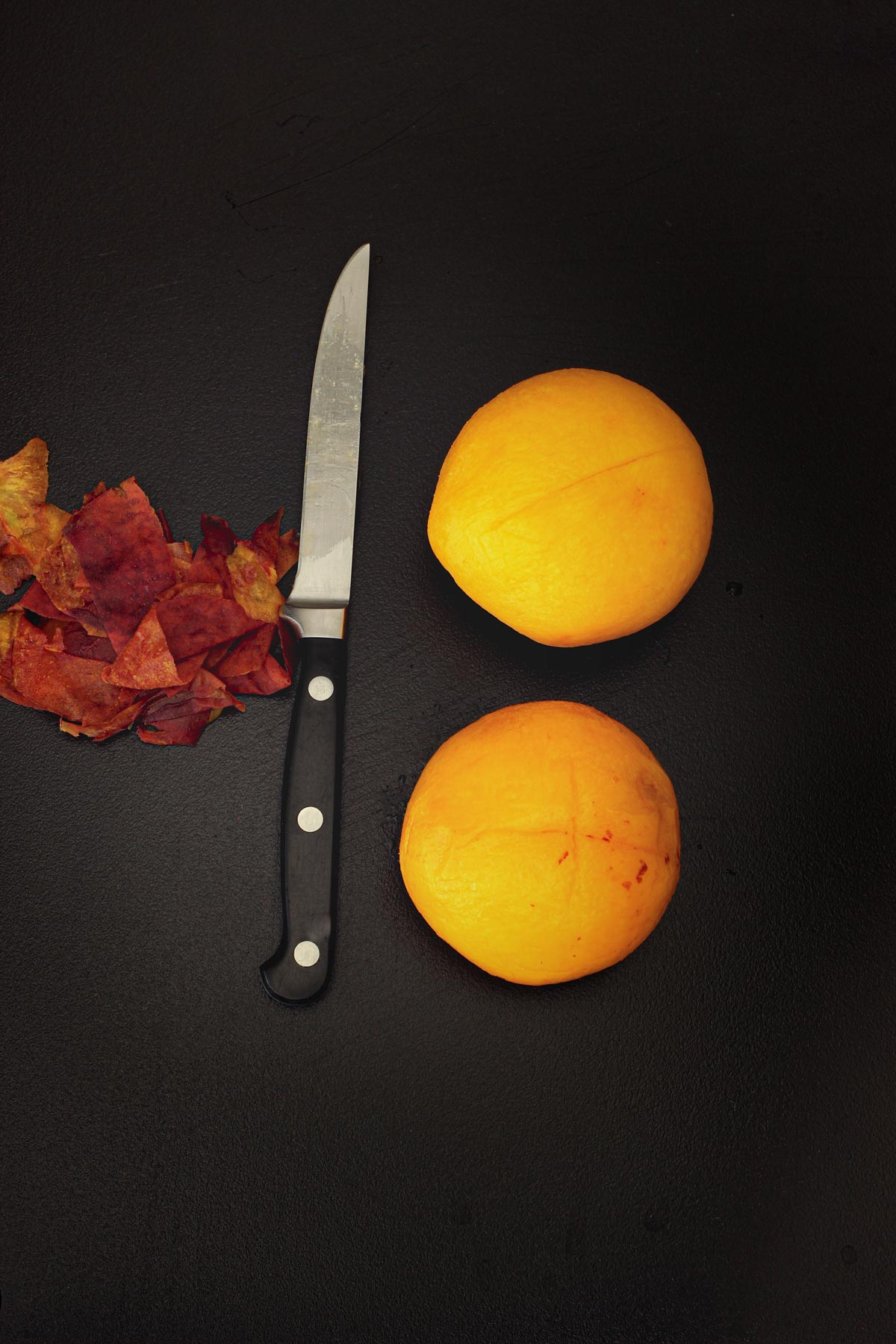 two peeled peaches on black table top next to knife and pile of skin.