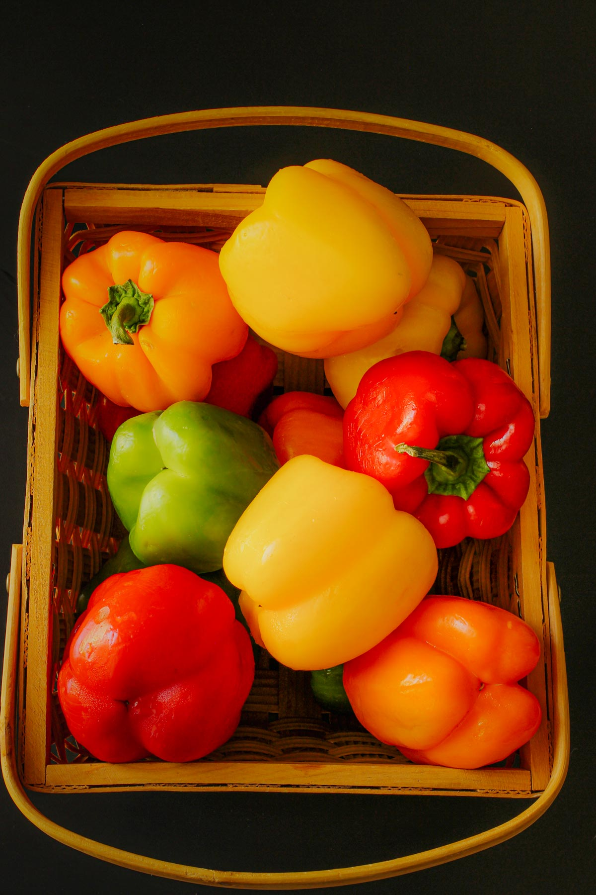 red, green, yellow, and orange bell peppers in a basket.