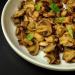 white plate of sauteed mushrooms sprinkled with basil leaves.