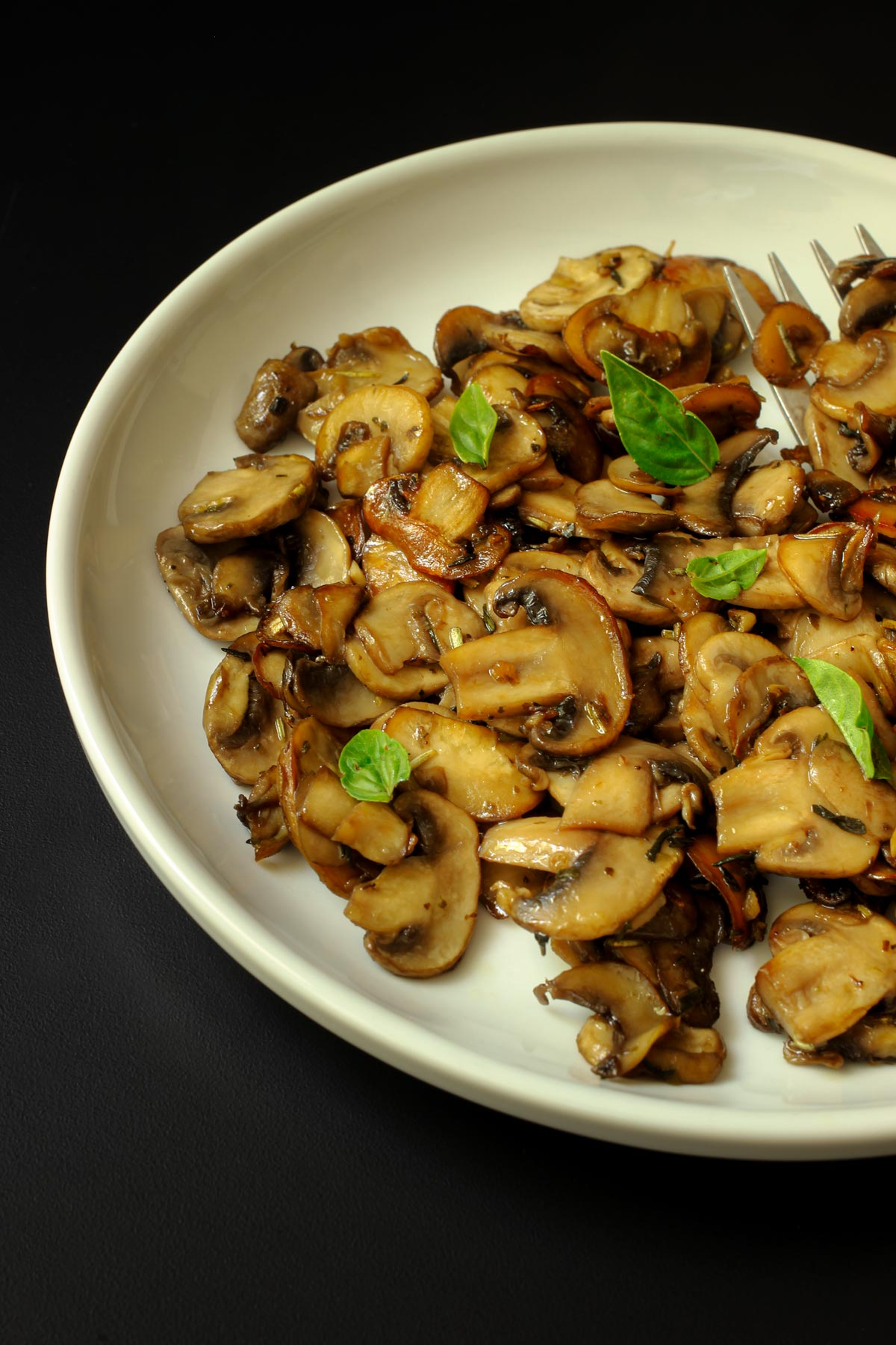 sauteed mushrooms with basil leaves on white plate.