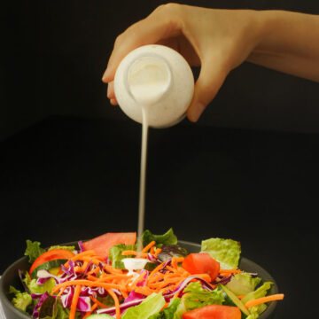 hand pouring buttermilk dressing onto salad.
