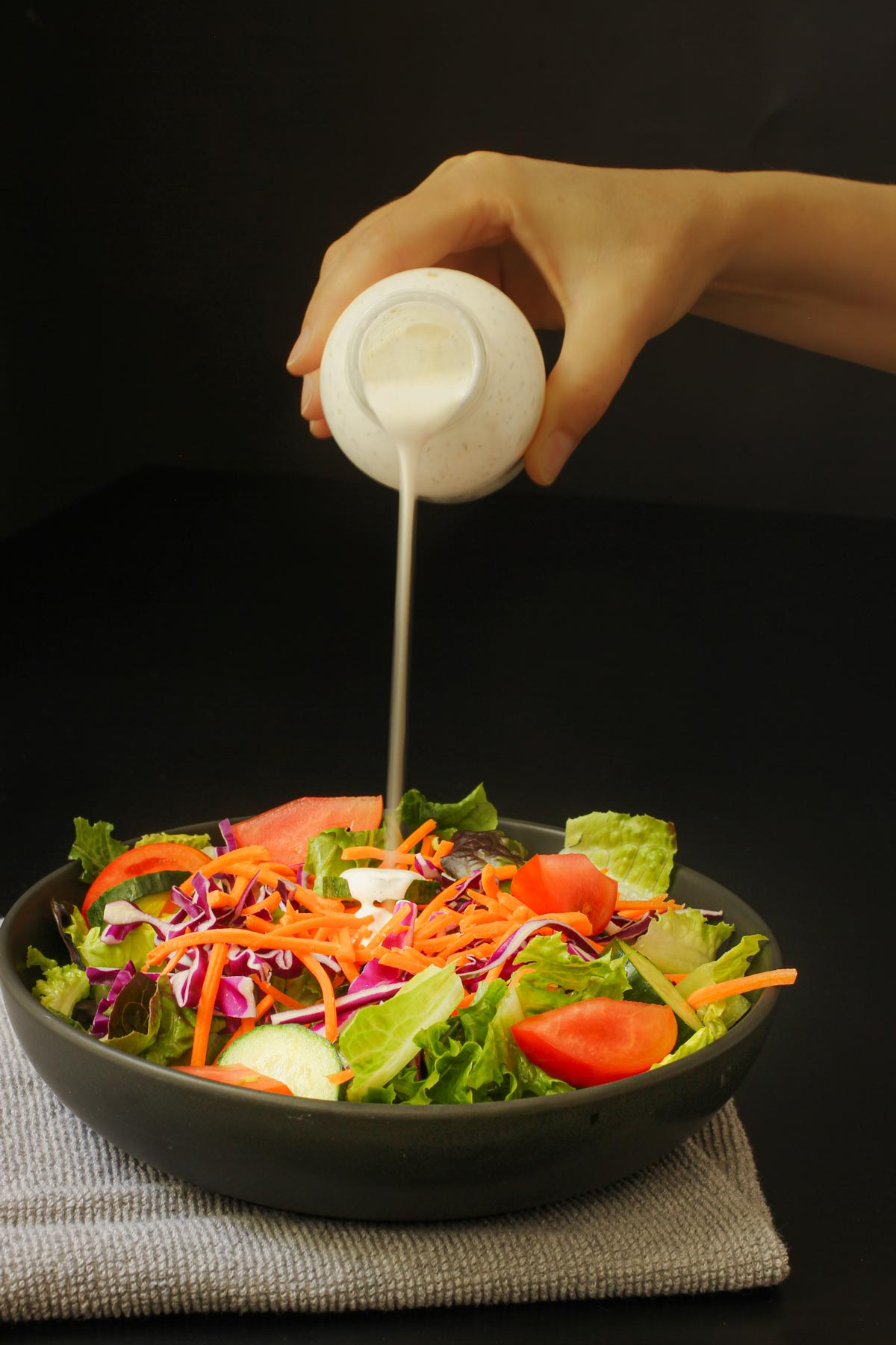 hand pouring buttermilk dressing onto green salad in black bowl.