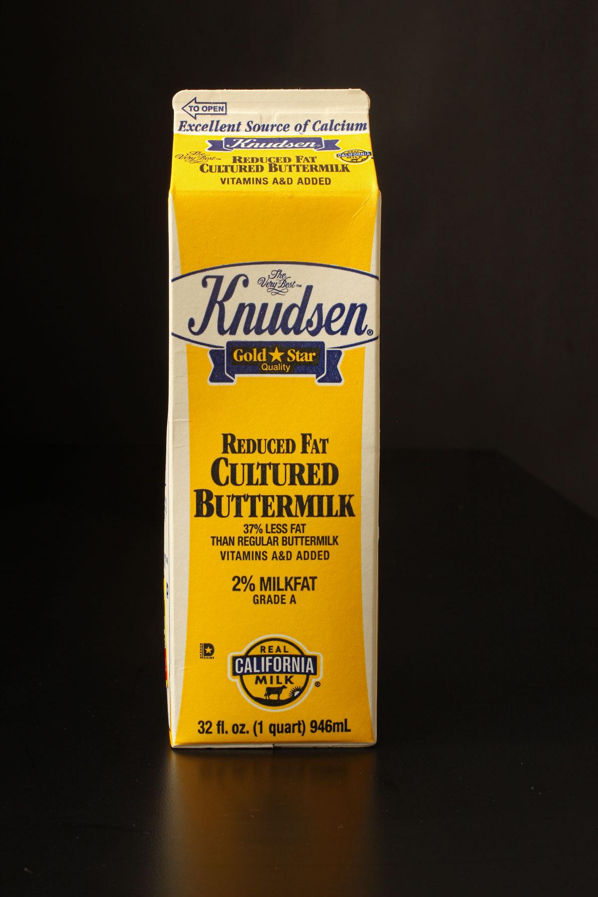 yellow quart carton of Knudsen buttermilk in front of black background.