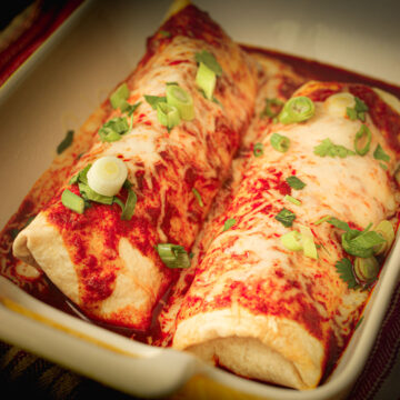 pair of chimichangas in baking dish topped with sauce, cheese, and chopped scallions.