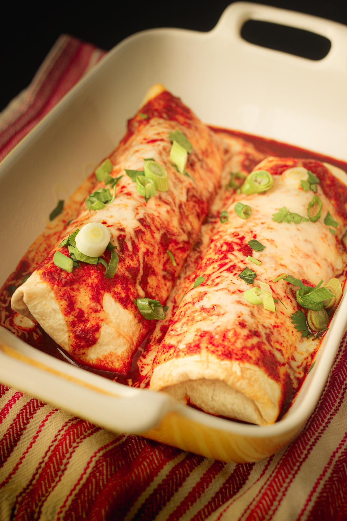 beef chimichangas in baking dish topped with sauce, cheese, and other toppings.