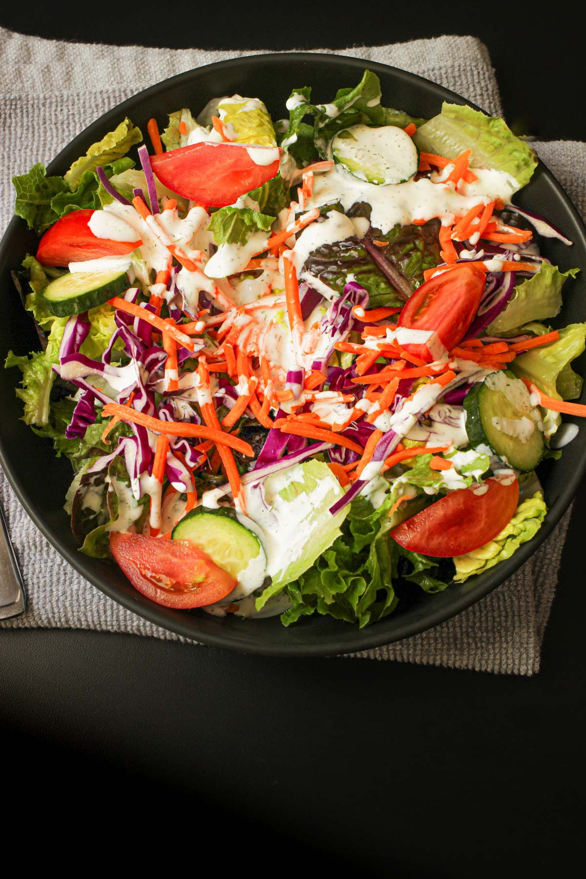 black salad bowl full of a green salad topped with buttermilk dressing.