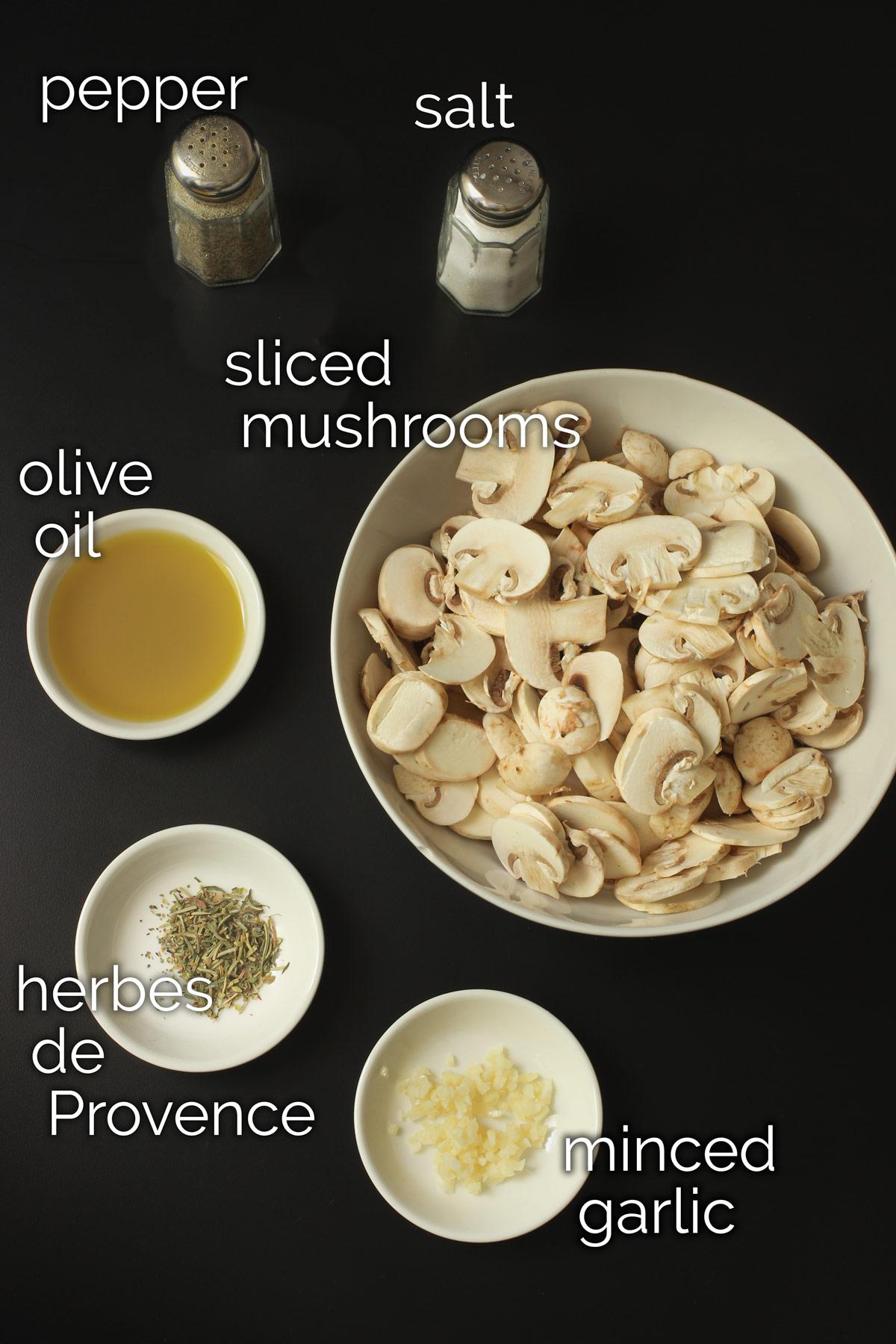 ingredients for sautéed mushrooms on black tabletop.