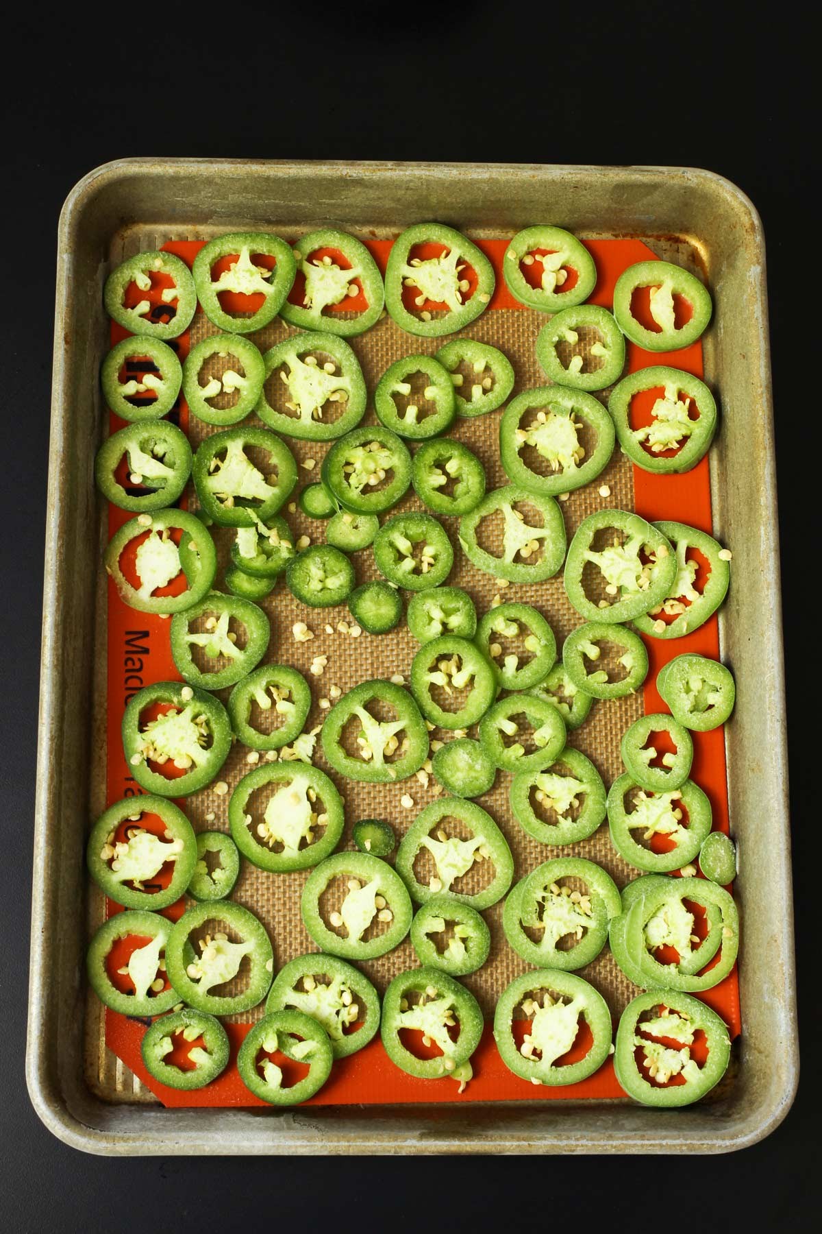 sliced jalapeños frozen on a tray lined with a silpat mat.