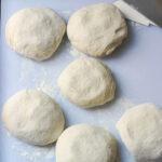 sourdough pizza dough balls on floured surface.
