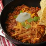 no bean chili recipe served in a black bowl topped with cheese, sour cream, green onions, and chips.