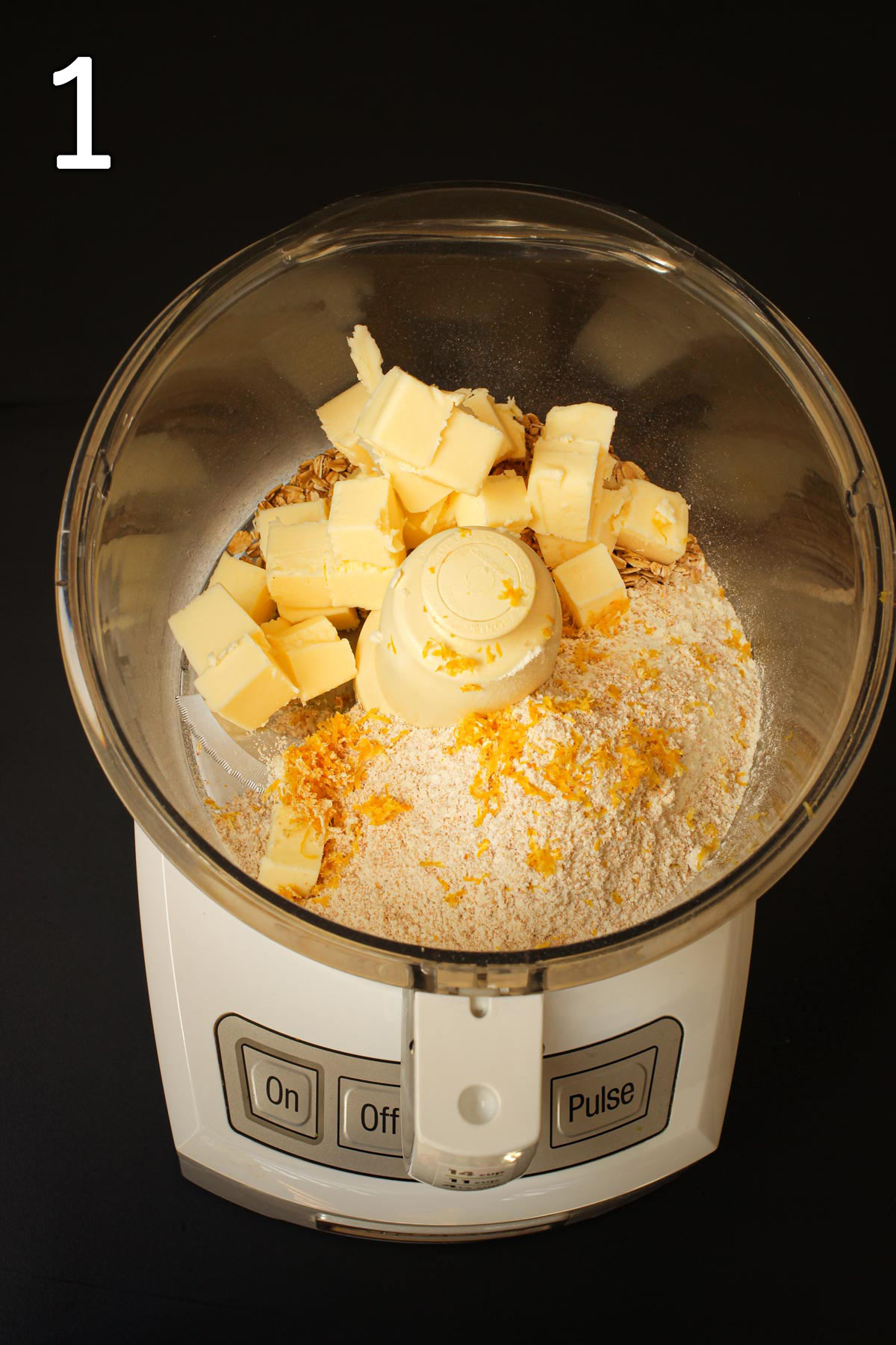 butter cubes, lemon zest, oats, and flour in bowl of food processor fitted with metal blade.