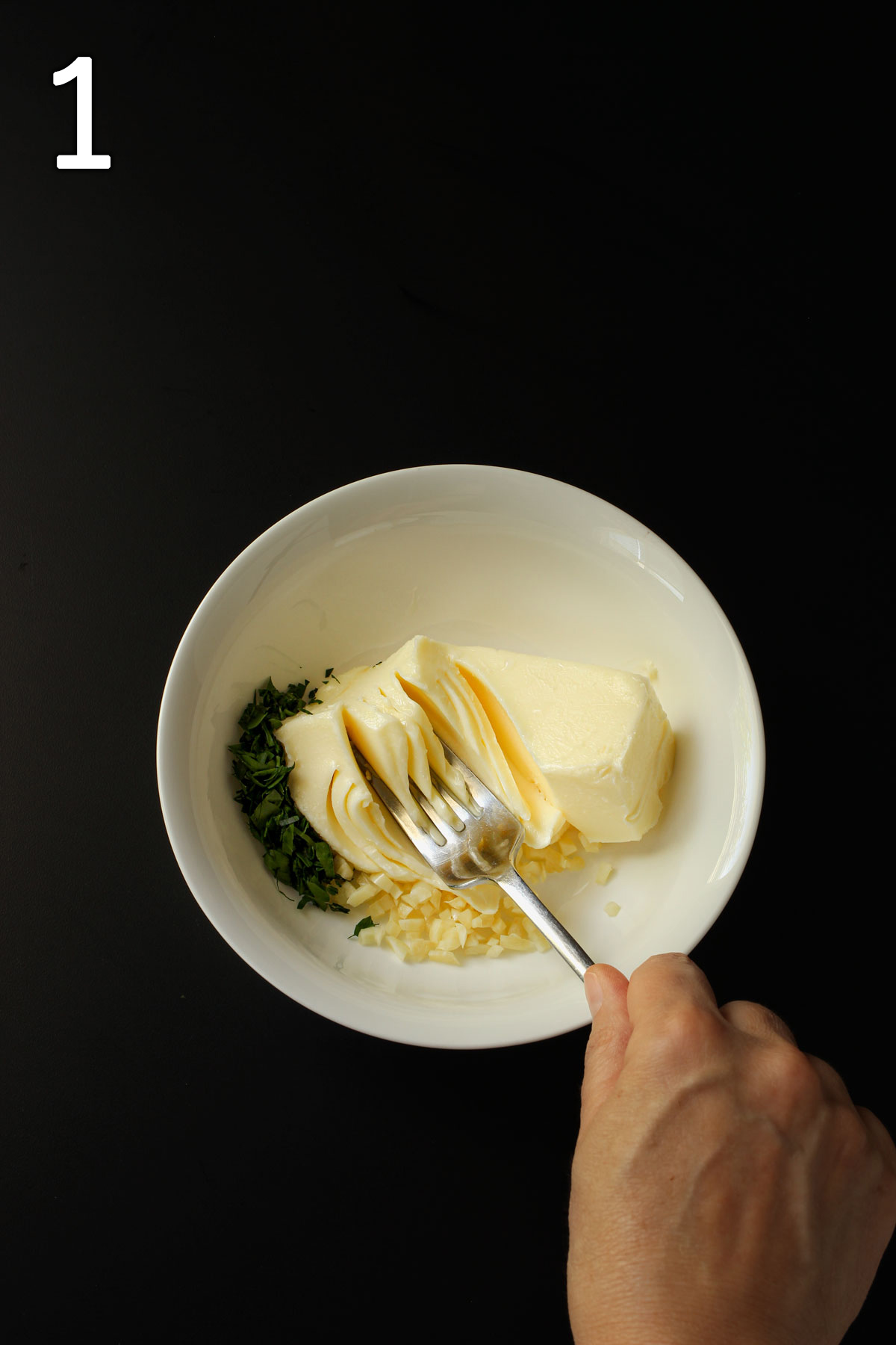 garlic and butter and parsley in a bowl with a hand smashing a fork into it.