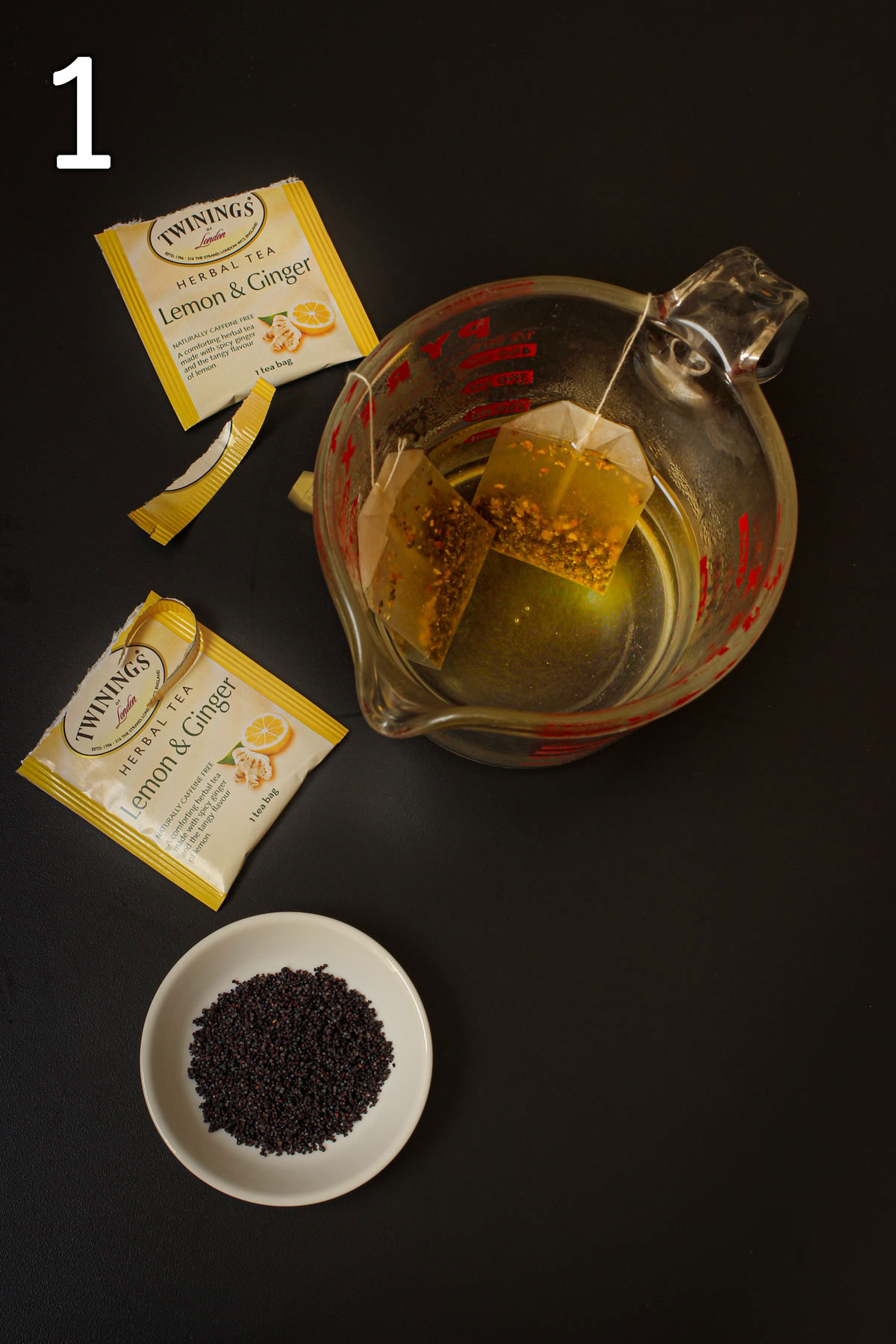 steeping tea and poppy seeds in glass measuring cup.