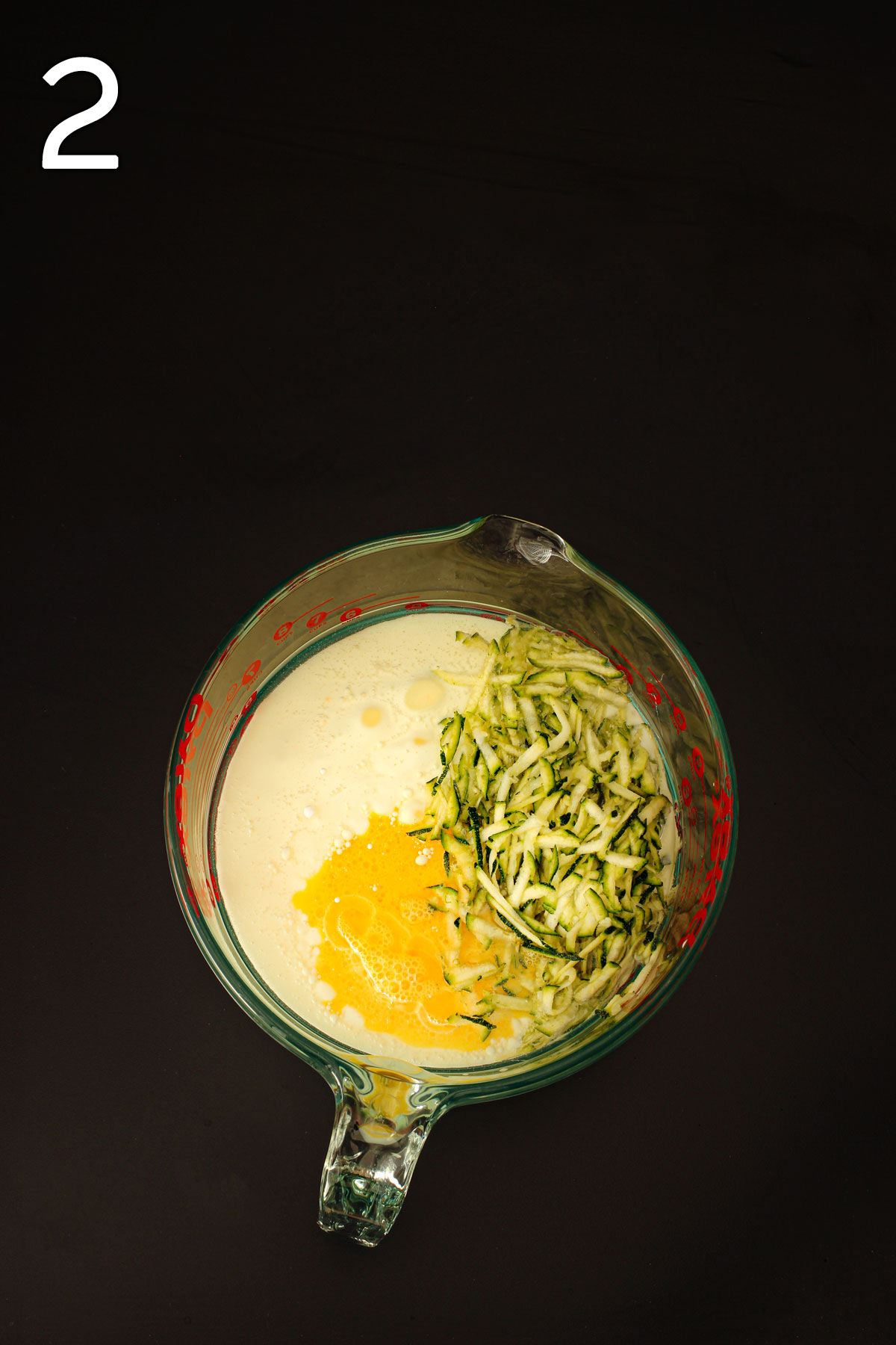 buttermilk, oil, eggs, and zucchini in pyrex mixing bowl.