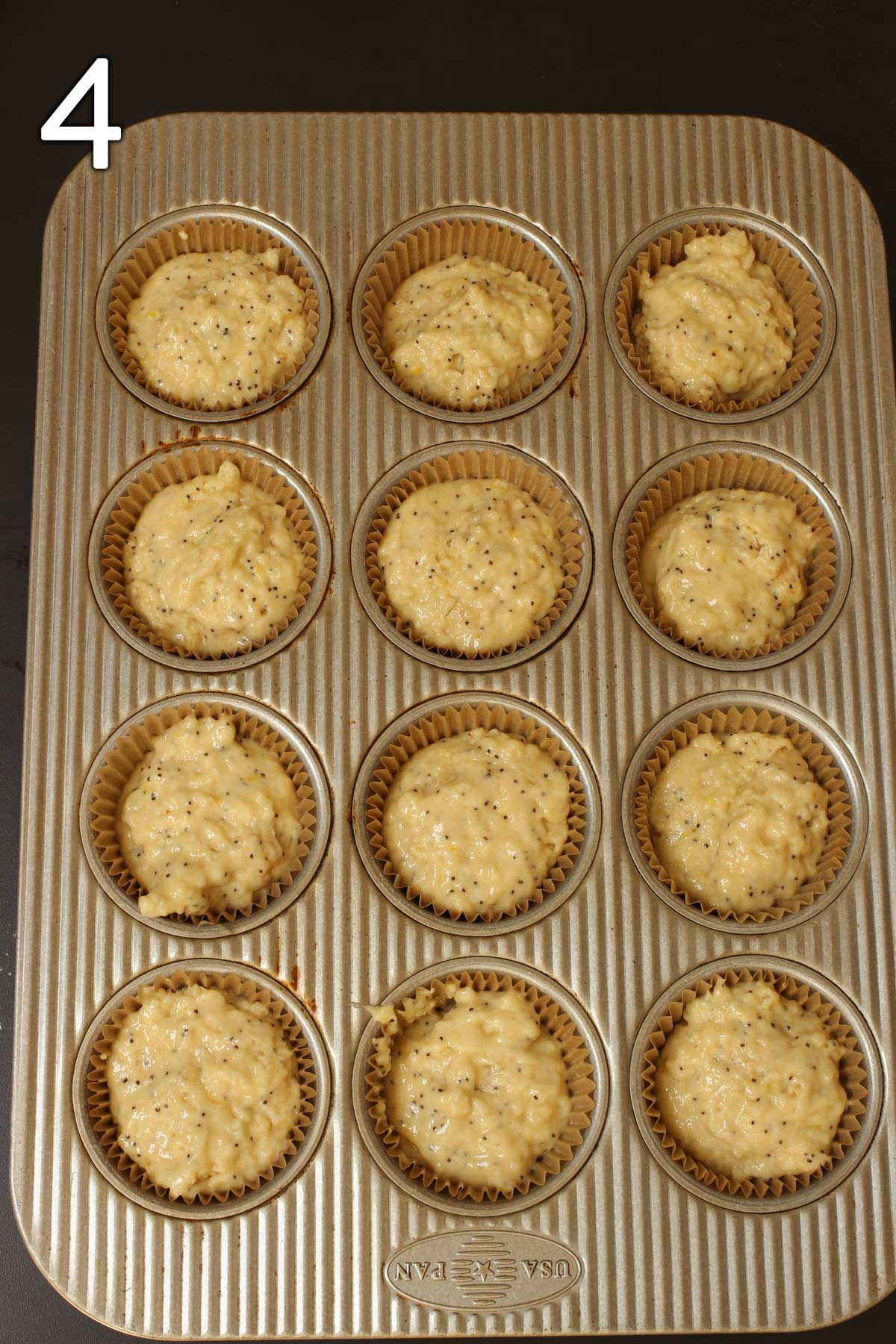 muffin batter divided into paper-lined tins.