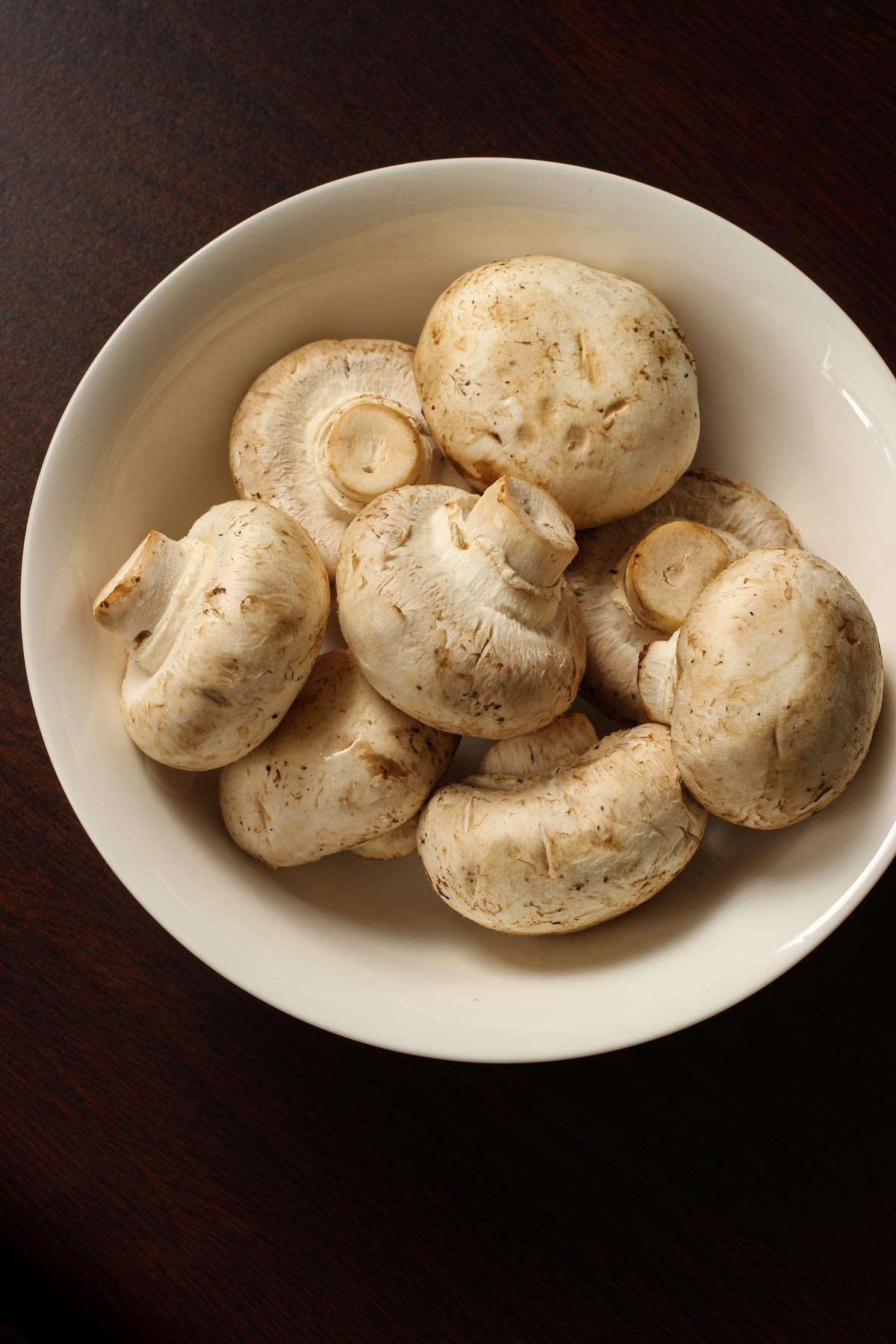 white bowl full of whole mushrooms.