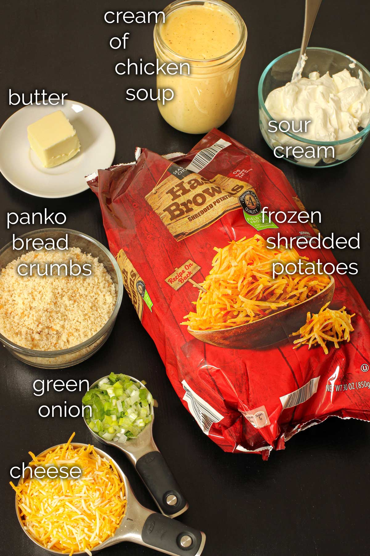 ingredients for cheesy hashbrown casserole on black table top.