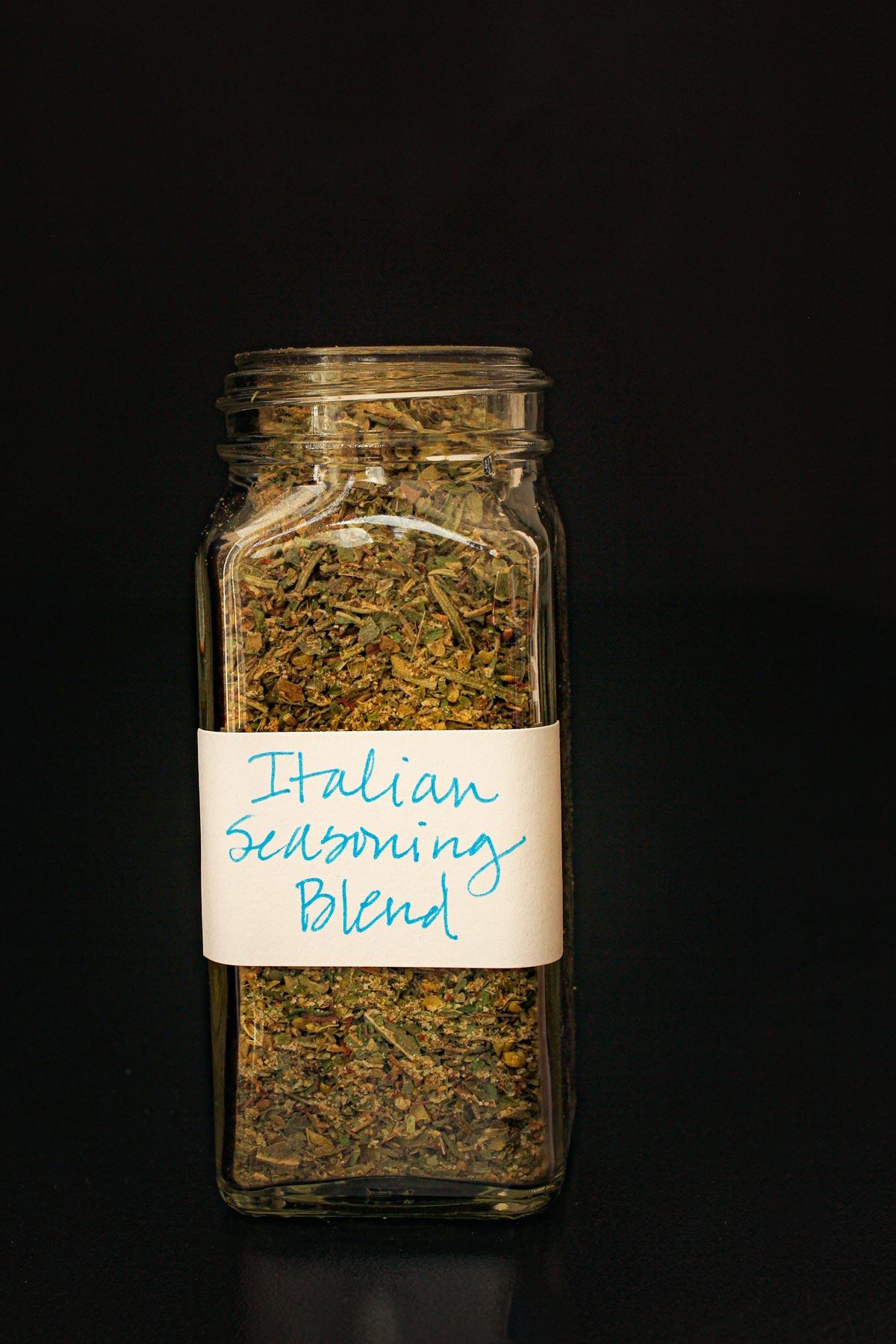 jar of homemade Italian seasoning with a hard-written label.