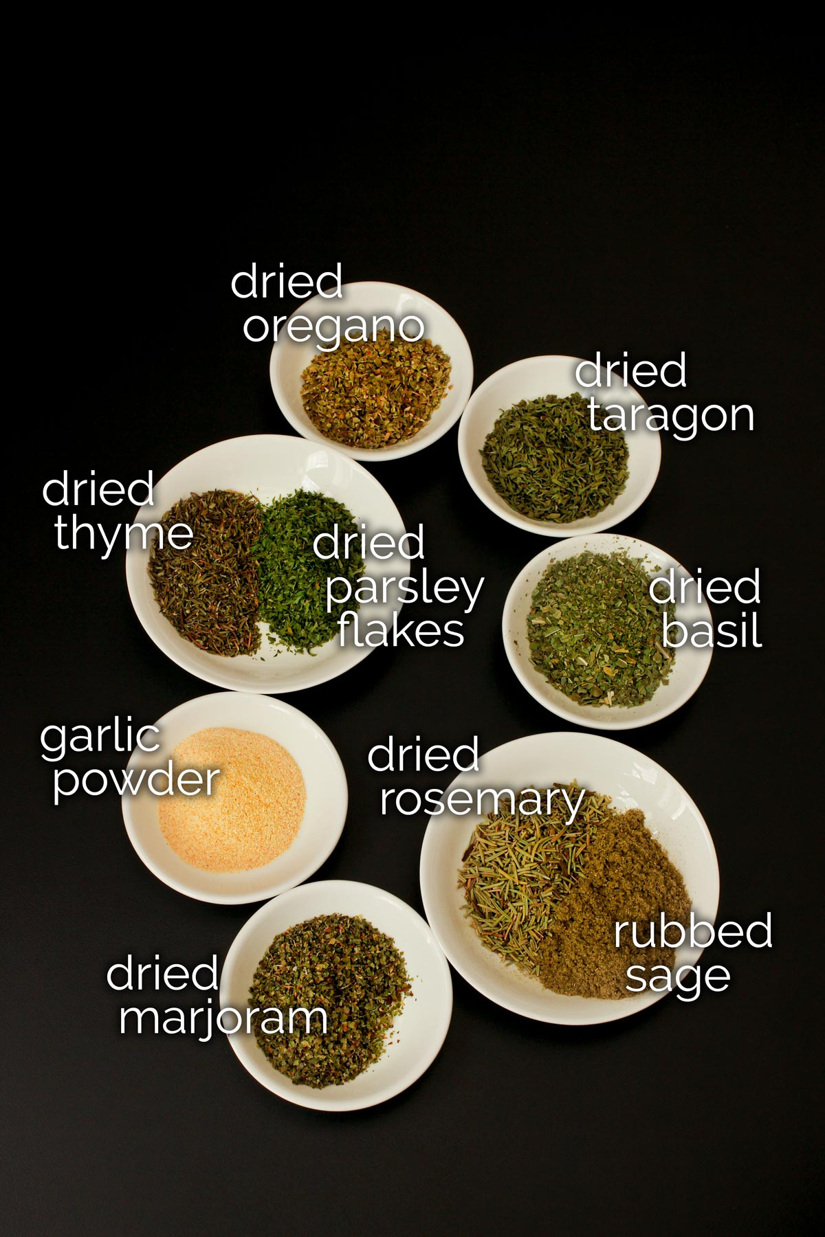 ingredients for Italian seasoning mix laid out in small white dishes on black table top.