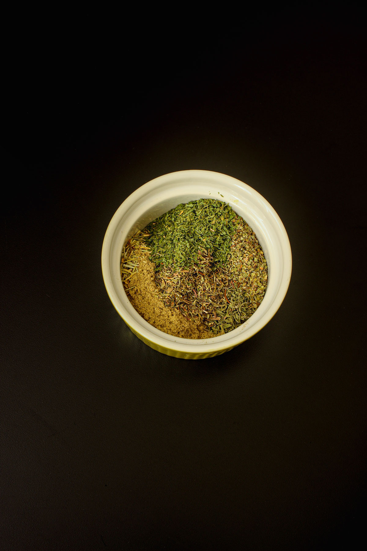 Italian herbs placed in small bowl.