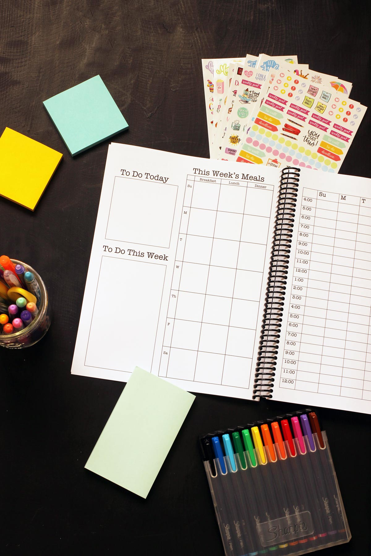 open Print & Go Planner with weekly meal plan blanks on table with stickers, post-it notes, and markers.