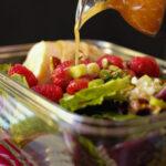 drizzling raspberry vinaigrette on raspberry salad.