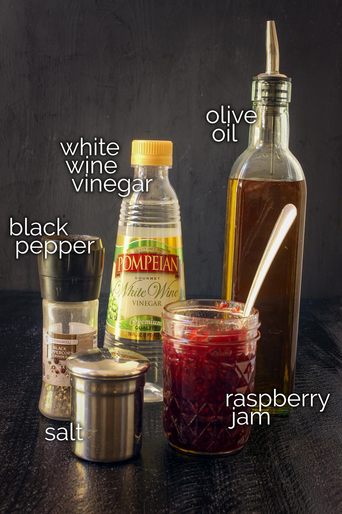 raspberry vinaigrette ingredients laid out on a black table top.
