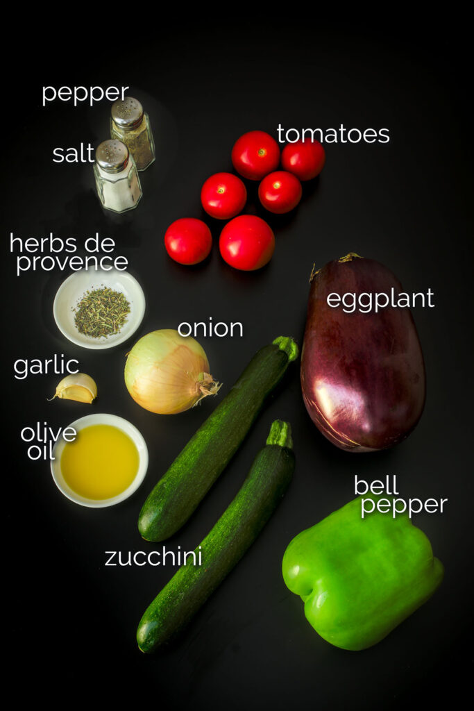 ingredients for ratatouille laid out on a black table top.