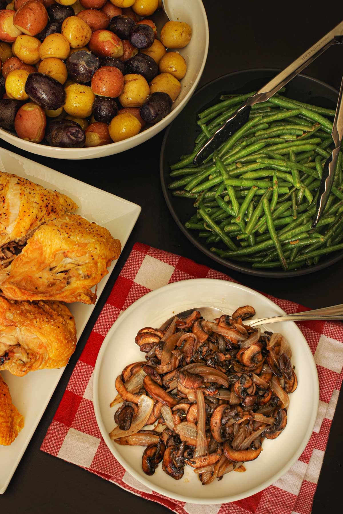 dinner table spread with platters of chicken, potatoes, green beans, and sautéed mushrooms and onions.