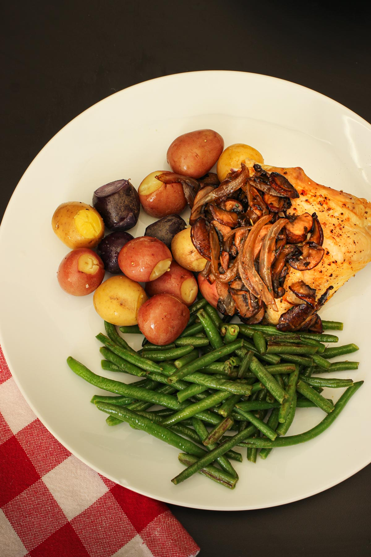 dinner plate with tri-color potatoes, chicken with sautéed mushrooms and onions, and green beans.