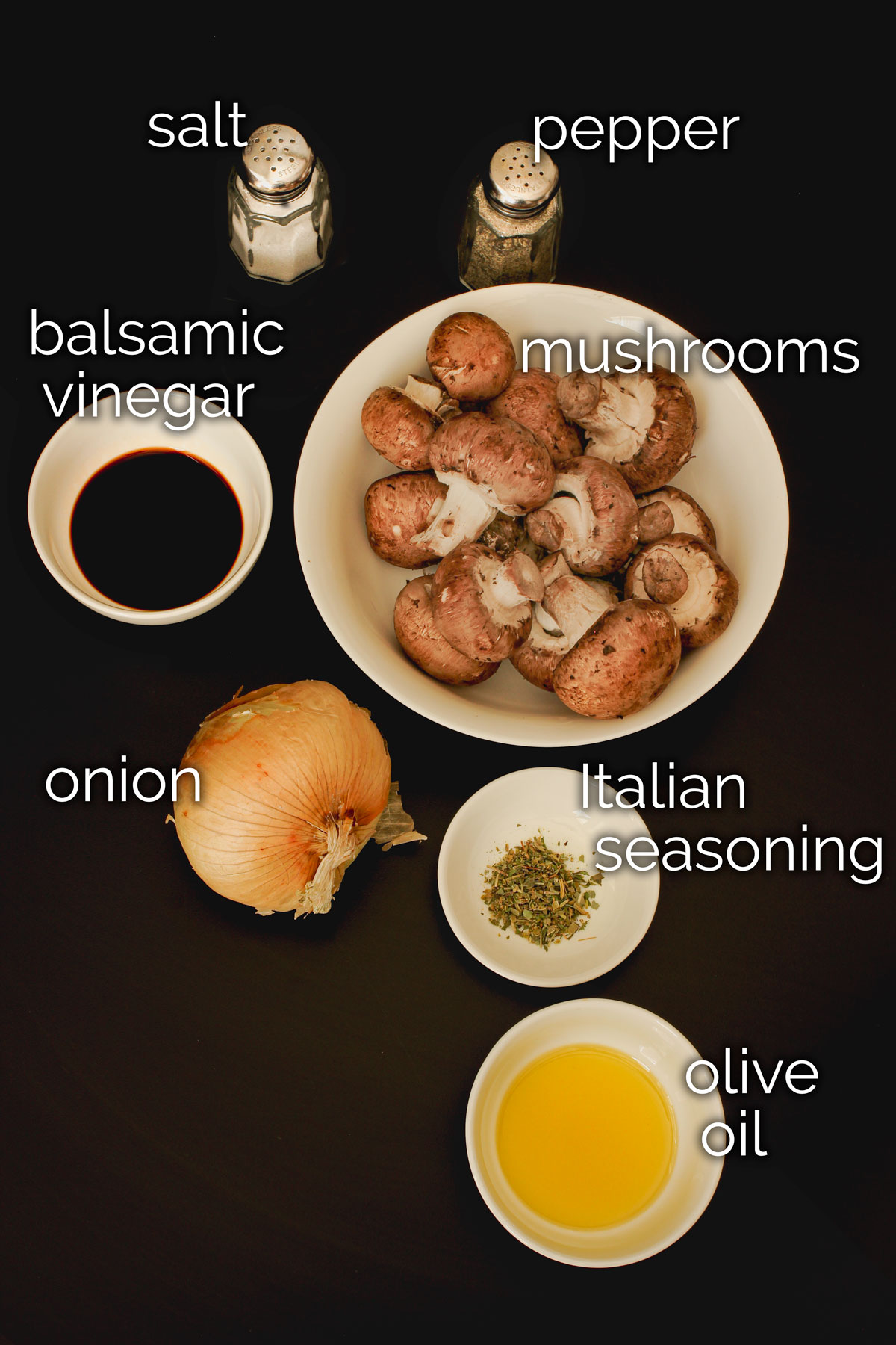 ingredients for sautéed mushrooms and onions laid out on a black table top.