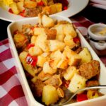 seasoned home fries in a rectangular dish with a spoon.