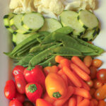 vegetable tray laid with cauliflower, cucumber, peas, peppers, and carrots.