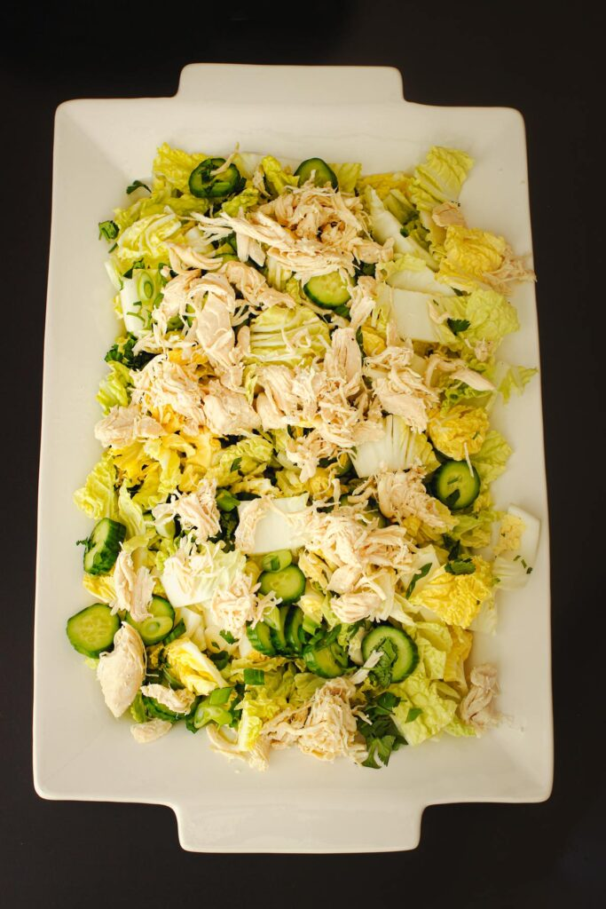 cucumbers and chicken added atop the cabbage on the serving platter.