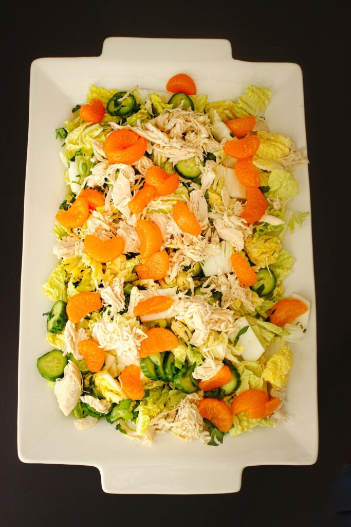 oranges added in a layer atop the salad on serving platter.