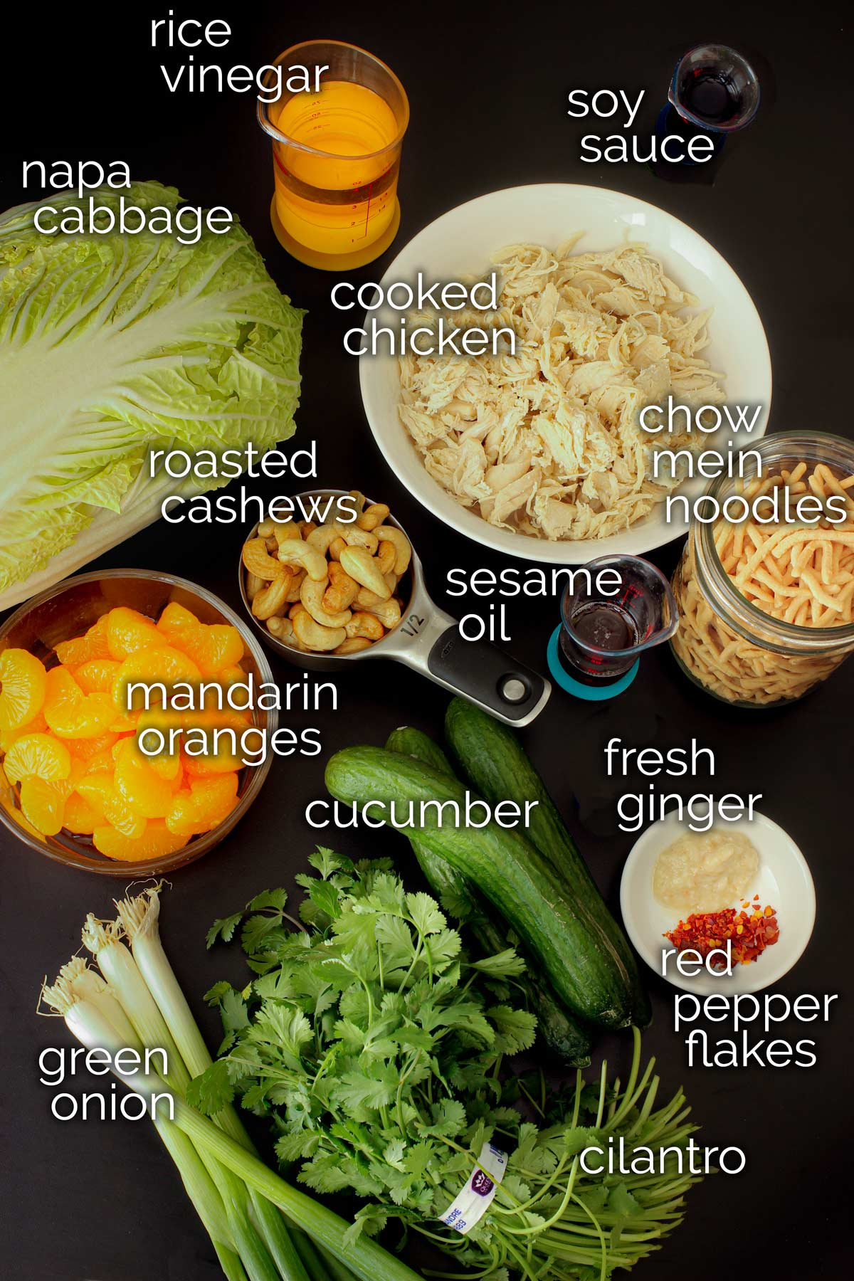 ingredients for asian cabbage salad laid out on black table top.