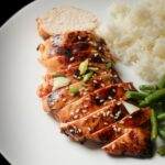 asian marinated chicken breast sliced on a plate with rice and veg.