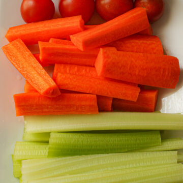 close up of carrot and celery sticks on white platter.