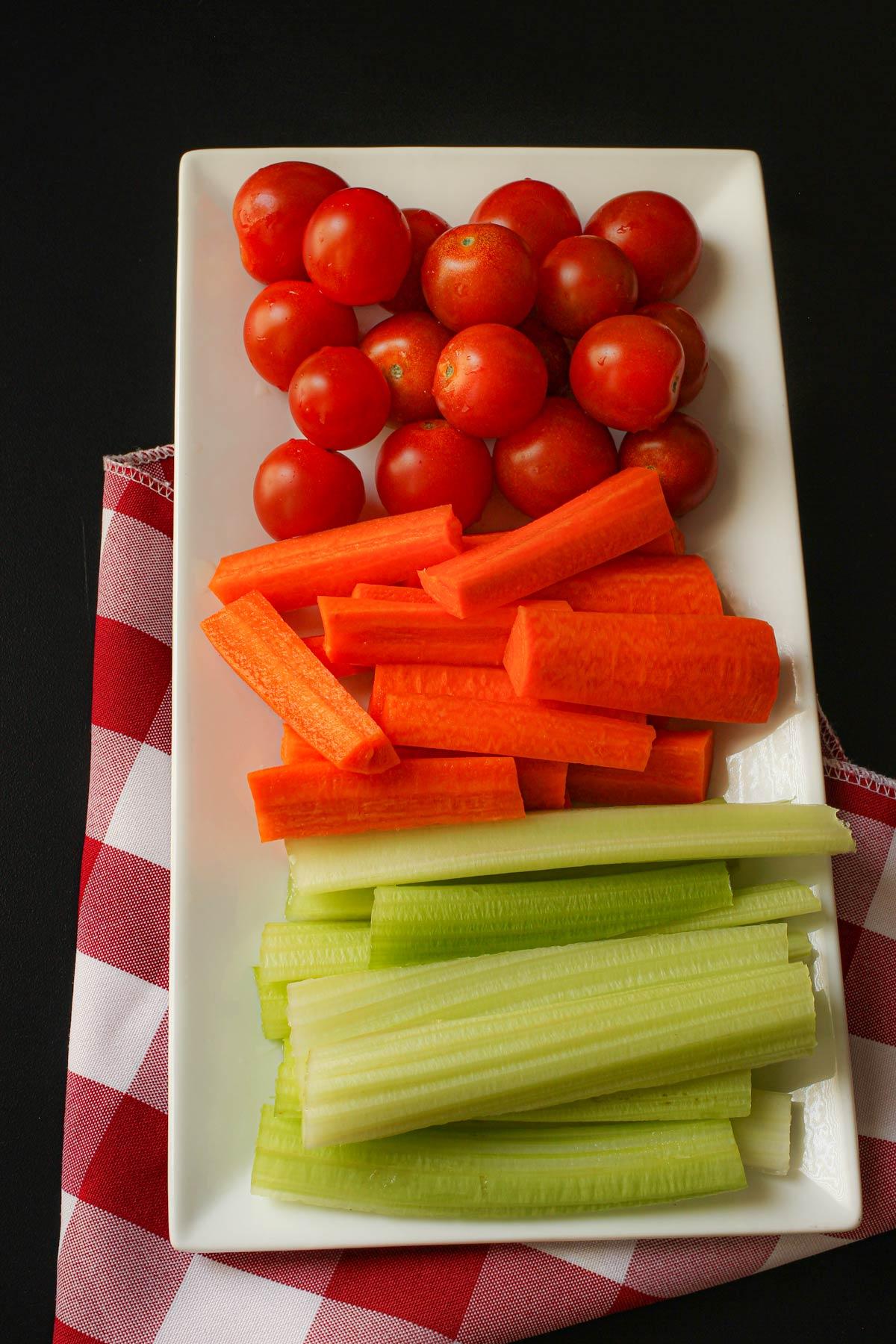 rectangular platter of cherry tomatoes, carrot sticks, and celery sticks.