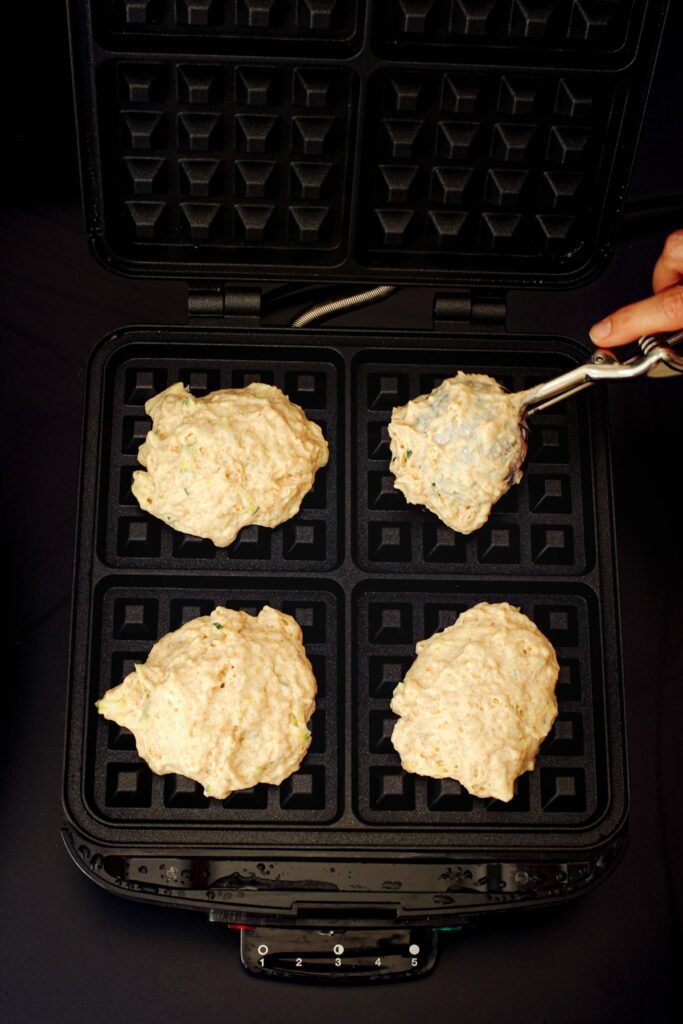 scooping waffle batter into waffle maker with cookie scoop.