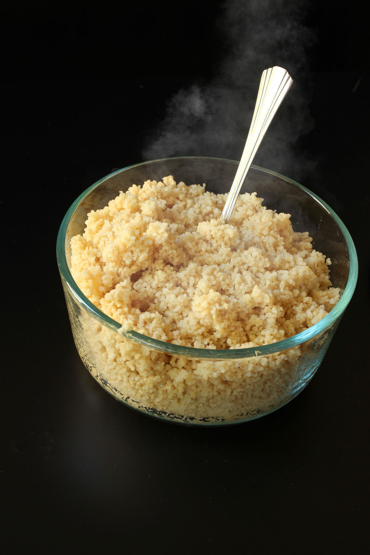 cooked couscous in a glass bowl with a fork.