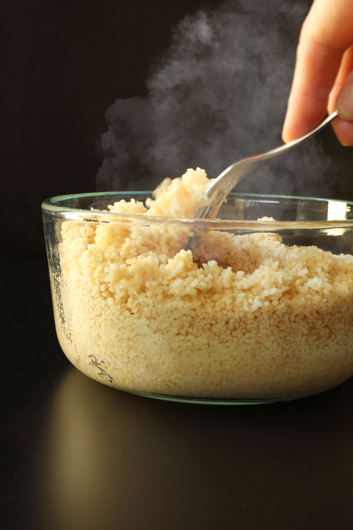 hand holding fork to break up cooked couscous in glass dish.