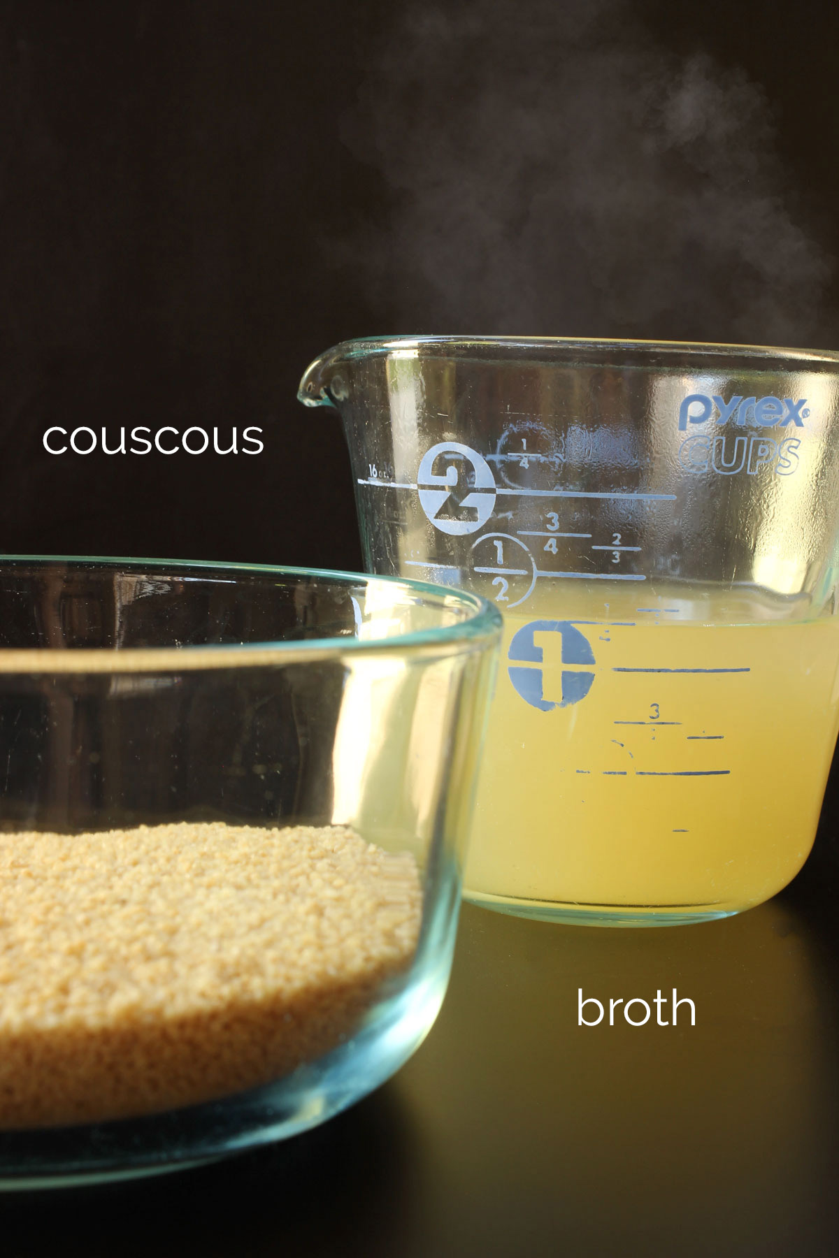 couscous in a glass dish next to hot chicken broth in a glass measuring cup.