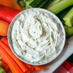 dill dip in small round dish on veggie tray.