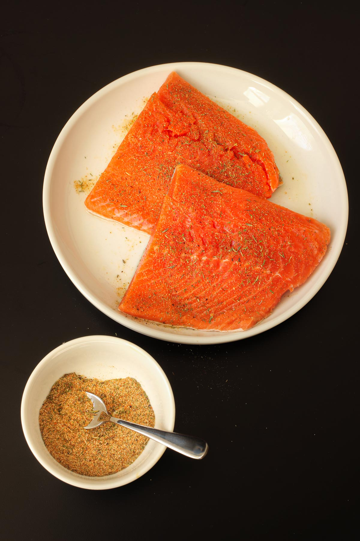 fish seasoning in a small dish next to a plate of salmon pieces.