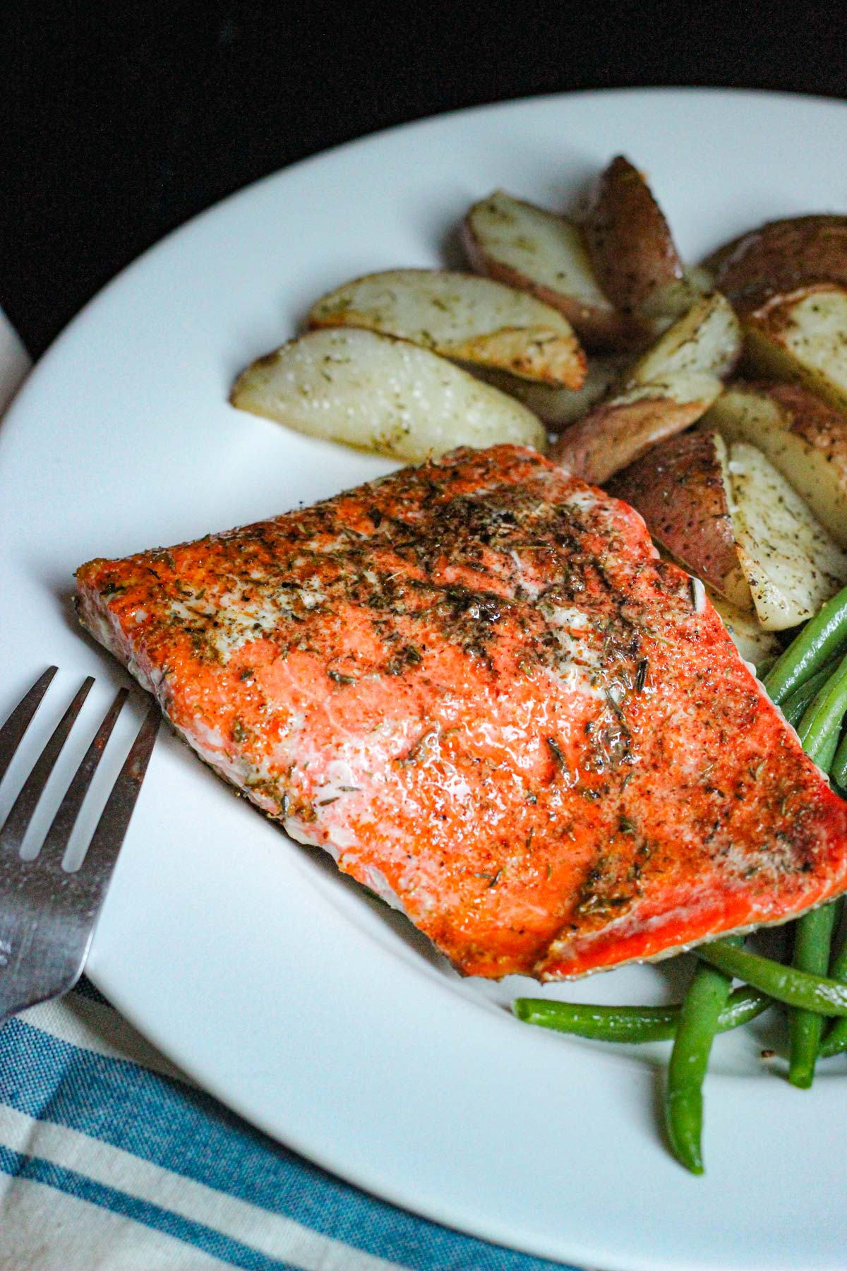 salmon with spicy fish seasoning plated with potatoes and green beans.