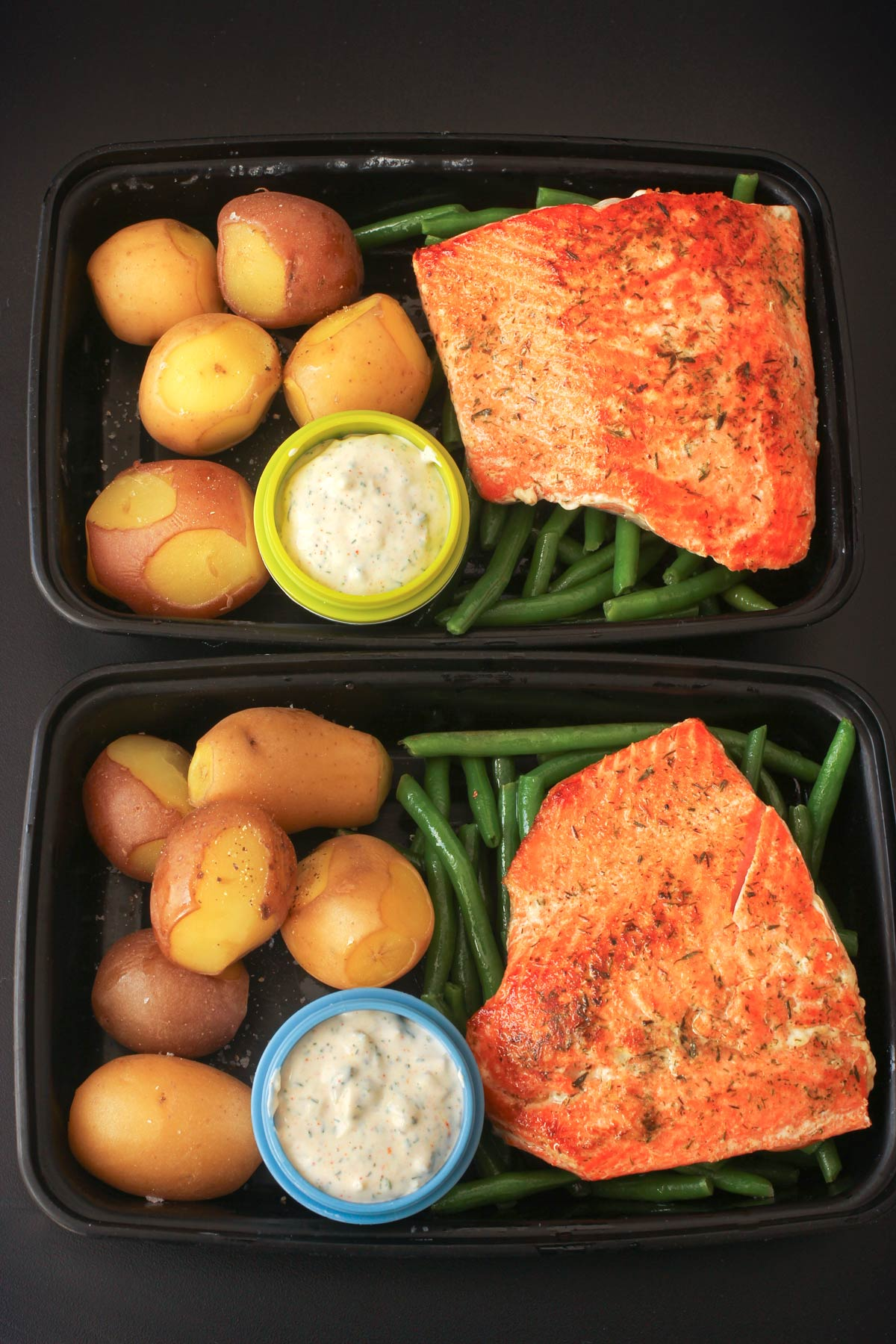 meal prep boxes with green beans, salmon, and potatoes with tartar sauce.