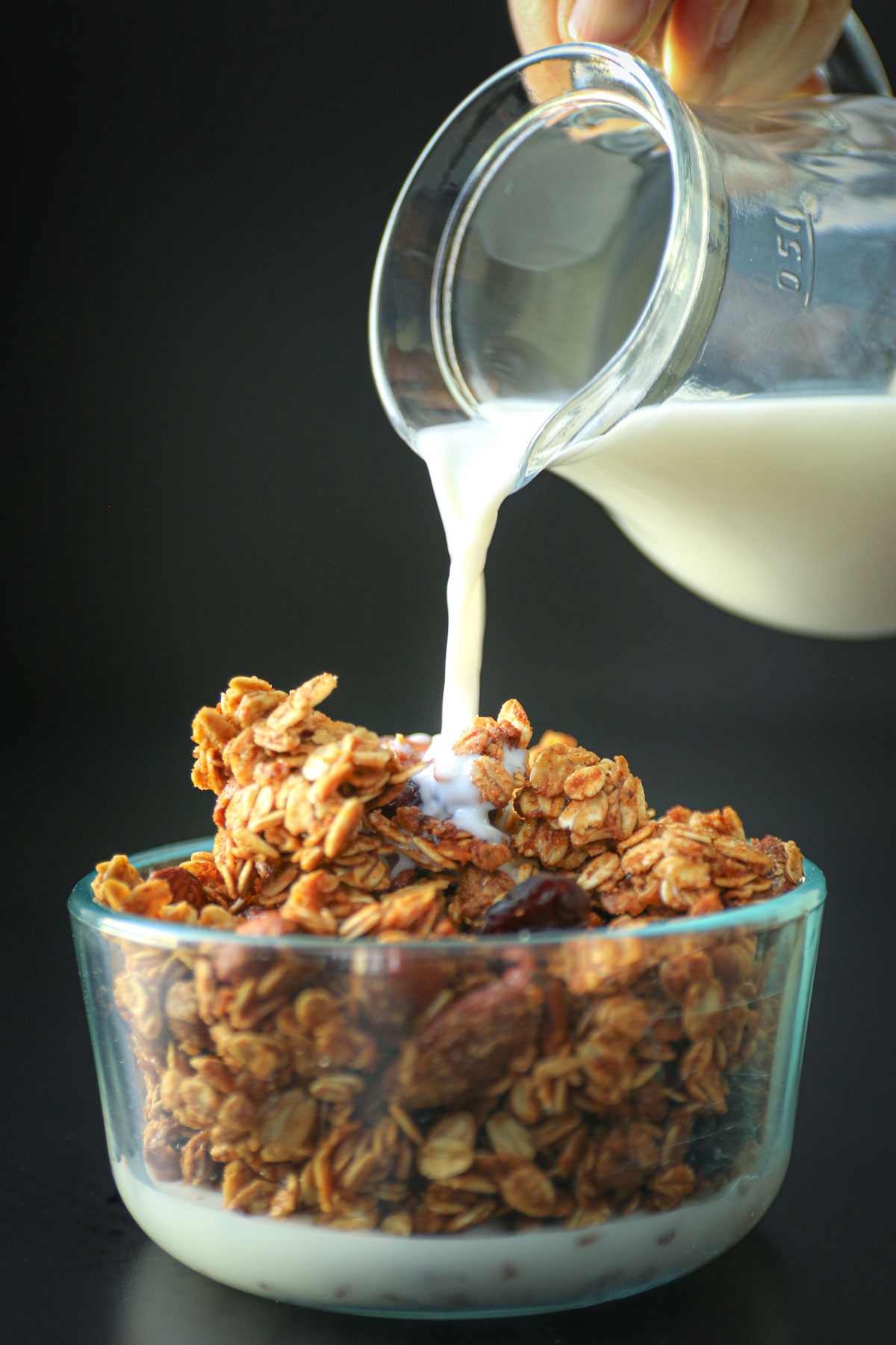 pouring milk from small glass pitcher into glass bowl of granola.